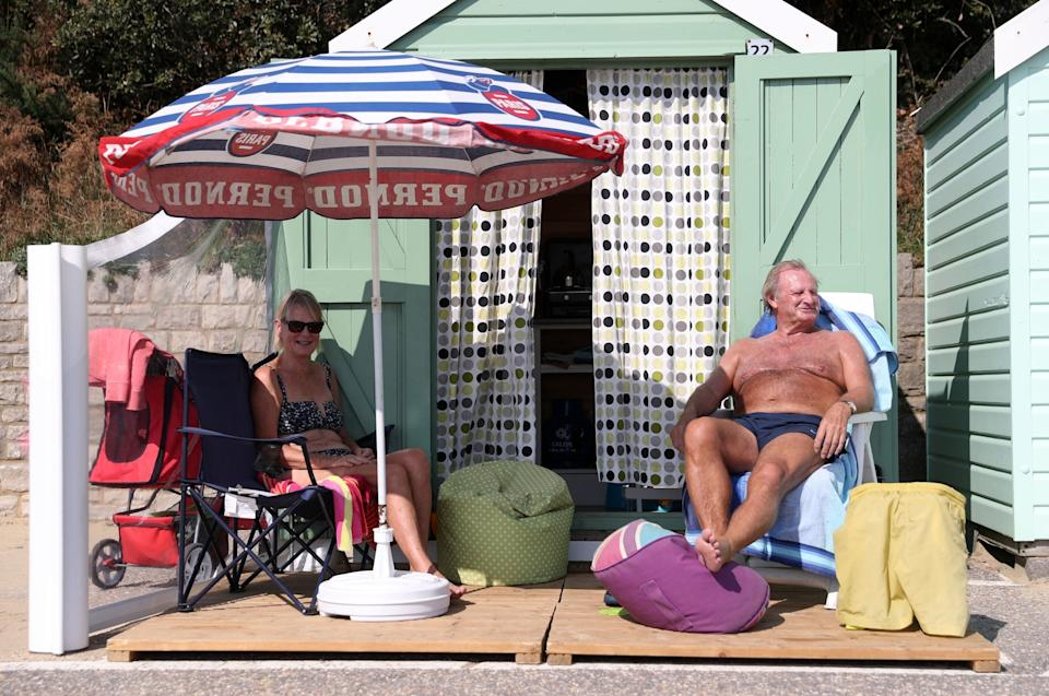 Rob Underhill (right) and his wife Sally sit outside their beach hut as they enjoy the Autumn sunshine on Bournemouth beach in Dorset: PA