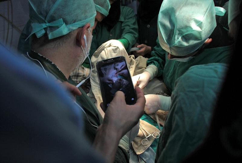 A surgeon holds a cell phone during surgery as he awaits a real-time consultation in Douma, a rebel-held town in the Eastern Ghouta region on October 11, 2017 (AFP Photo/Hamza Al-Ajweh)