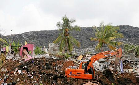 Military officers operate an excavator during a rescue mission after a garbage dump collapsed and buried dozens of houses in Colombo