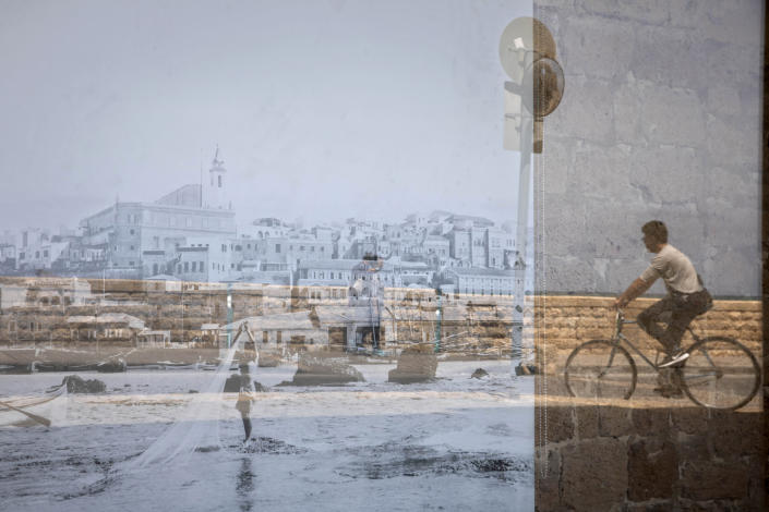 A man riding his bicycle is reflected on an old picture of Jaffa displayed in a window, in the Jaffa neighborhood of Tel Aviv, Israel, Wednesday, April 21, 2021. Historic Jaffa's rapid gentrification in recent years is coming at the expense of its mostly Arab lower class. With housing prices out of reach, discontent over the city's rapid transformation into a bastion for Israel's ultra-wealthy is reaching a boiling point. (AP Photo/Sebastian Scheiner)