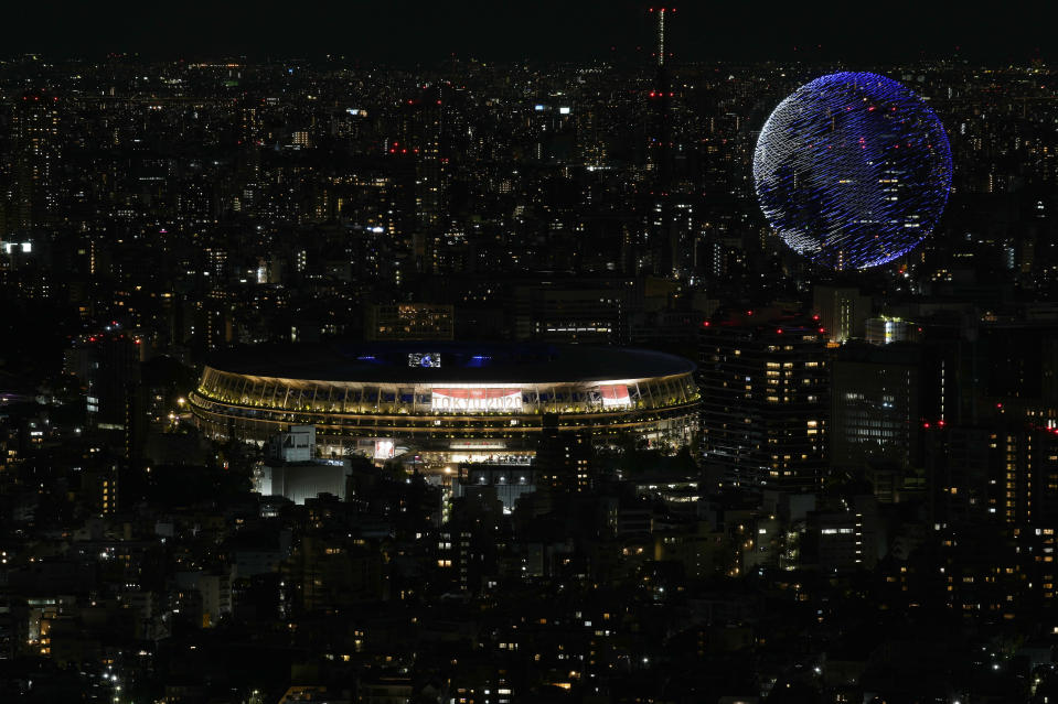 Drones flying over the National Stadium during the opening ceremony of 2020 Tokyo Olympics is seen from Shibuya Sky observation deck Friday, July 23, 2021, in Tokyo, Japan. (AP Photo/Eugene Hoshiko)