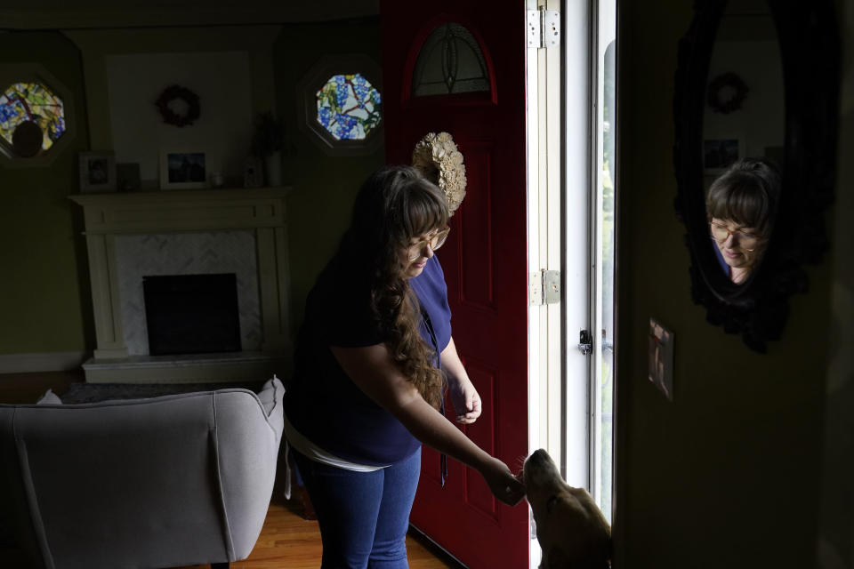 Allison Cullen, of Brockton, Mass., greets the family dog Lula, right, Thursday, July, 22, 2021, after speaking on the phone with her husband Flavio Andrade Prado, a Brazilian national, from their home in Brockton. Prado is being held by Immigration and Customs Enforcement, or ICE, at the Plymouth County House of Corrections. The number of detainees nationwide has more than doubled since the end of February, to nearly 27,000, according to recent data from U.S. Immigration and Customs Enforcement. (AP Photo/Steven Senne)
