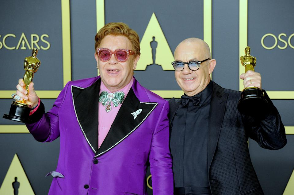 "Sir Elton John and Bernie Taupin pose with their Awards for Best Original Song, ""I'm Gonna Love Me Again"" ('Rocketman') inside The Press Room of the 92nd Annual Academy Awards held at Hollywood and Highland on February 9, 2020 in Hollywood, California.  (Photo by Albert L. Ortega/Getty Images)"