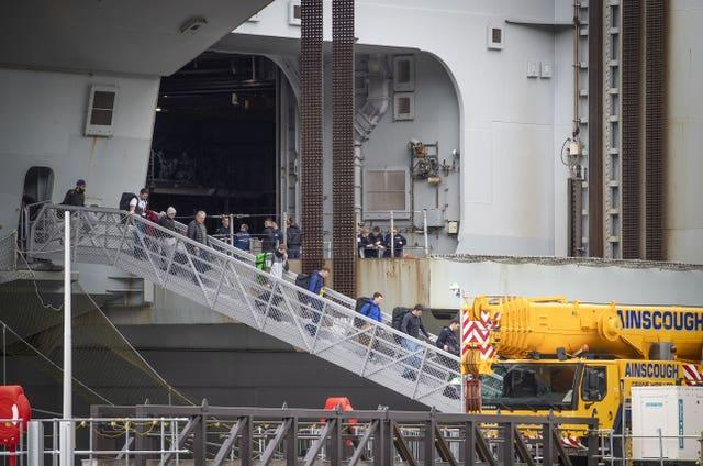 Crew members disembark from the Royal Navy aircraft carrier HMS Queen Elizabeth (Jane Barlow/PA)