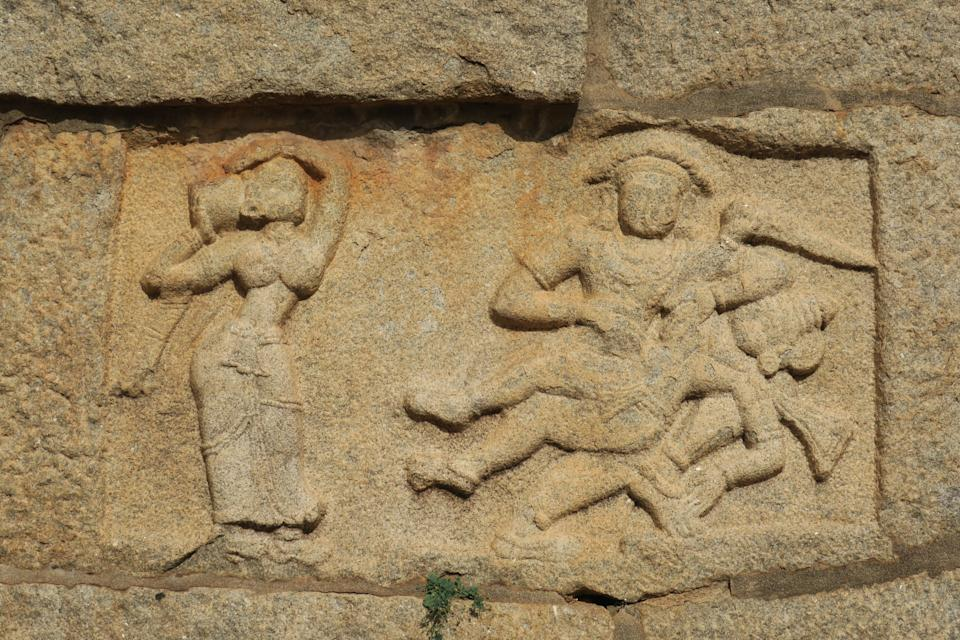 Sculpture of Bhima killing Dushasana with Draupadi looking at it. This depicts a tale from Mahabharatha. The sculpture is present at Bhima's Gate, Hampi, India