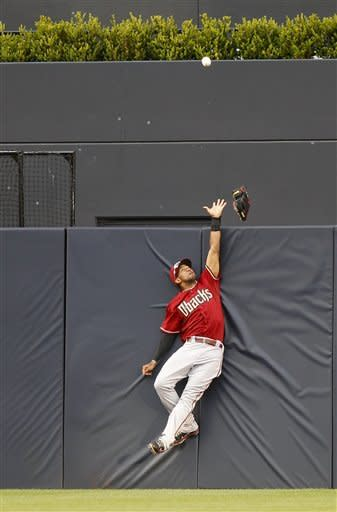Arizona Diamondbacks center fielder Chris Young loses his glove while leaping at the fence trying to catch a two-run home run by San Diego Padres' Chris Denorfia in the eighth inning of a baseball game won by the Padres 2-1 on Wednesday, April 11, 2012, in San Diego. (AP Photo/Lenny Ignelzi)