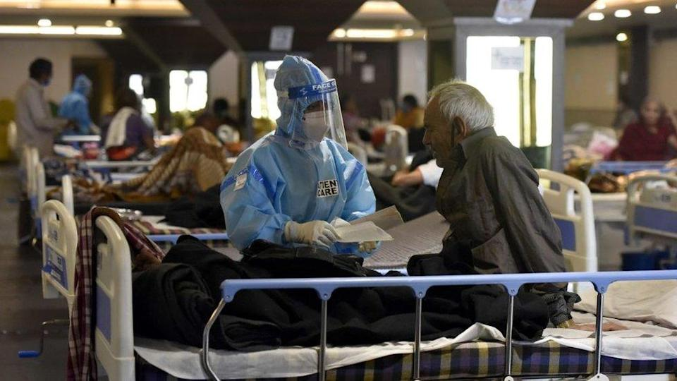 Medical staff in PPE coveralls attend to patients housed in the Shehnai Banquet Hall Covid-19 care centre attached to LNJP Hospital on April 15, 2021 in New Delhi, India.
