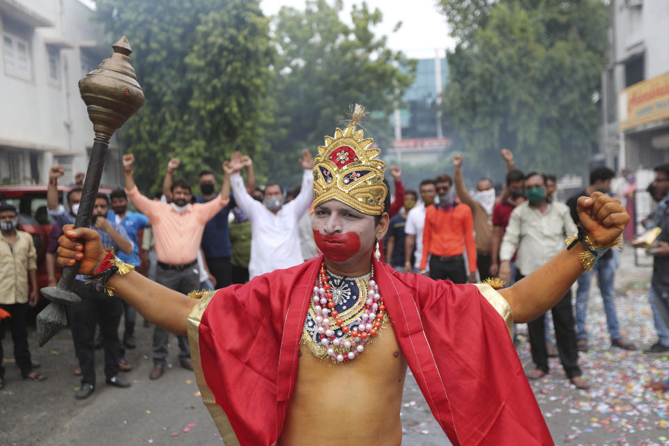 A man dressed as Hindu god Hanuman participates in a celebration by Vishwa Hindu Parishad or World Hindu Council to mark the groundbreaking ceremony of a temple dedicated to Hindu god Ram in Ayodhya, in Ahmedabad, India, Wednesday, Aug. 5, 2020. Despite the coronavirus restricting a large crowd, Hindus rejoiced as Indian Prime Minister Narendra Modi broke ground Wednesday on a long-awaited temple of their most revered god Ram at the site of a demolished 16th century mosque. (AP Photo/Ajit Solanki)
