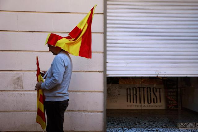 <p>A man prepares a Spanish flag before taking part on a rally against Catalonia's declaration of independence, in Barcelona, Spain, Sunday, Oct. 29, 2017. (Photo: Gonzalo Arroyo/AP) </p>