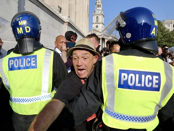 Members of StandUpX community who are anti-vaccine and are against the novel coronavirus (COVID-19) measures, gather at Trafalgar Square to stage for a protest, face off with police officers, in London.