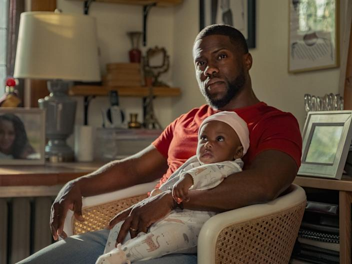 Kevin Hart sitting with baby.