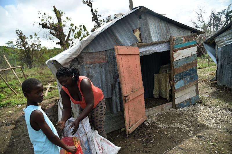 Sasa (R) and her son pictured on October 22, 2016 outside their house in Gebeaux in the city of Jeremie, southwestern Haiti, which was hit hard by Hurricane Matthew (AFP Photo/Hector Retamal)