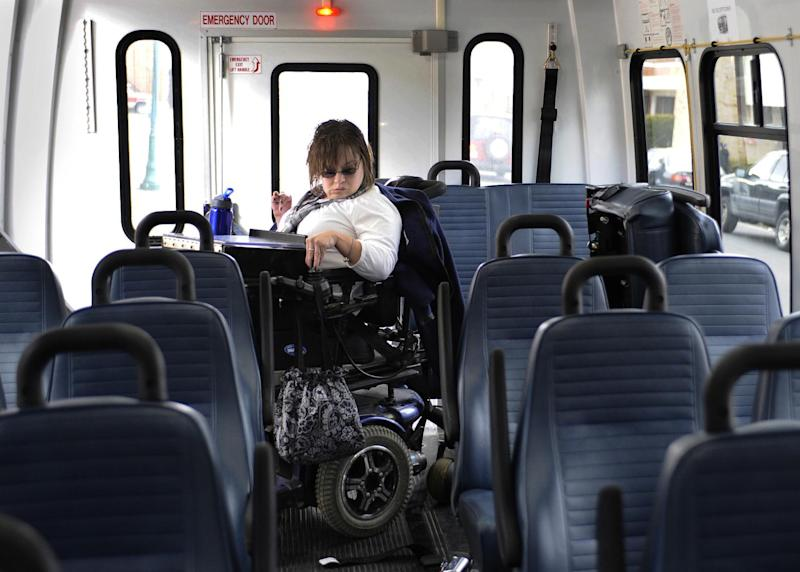 In this photo taken Friday, March 1, 2013, Jennifer Lortie maneuvers herself into a bus during her two-hour commute home after work in Willimantic, Conn. Of the 29 million working–age Americans with a disability Lortie, who has limited arm and leg use due to cerebral palsy, is one of the 5.1 million disabled Americans who are actually employed. The National Council on Disability's Jeff Rosen says long-standing prejudicial attitudes need to be addressed to boost jobs. (AP Photo/Jessica Hill)