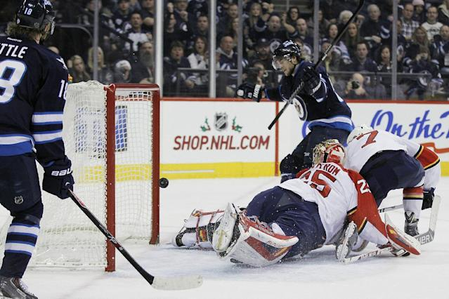 Winnipeg Jets' Michael Frolik, back, scores on Florida Panthers goaltender Jacob Markstrom (25) and Dmitry Kulikov (7) as Jets' Bryan Little, left, is near during the second period of an NHL hockey game in Winnipeg, Manitoba on Friday, Dec. 20, 2013. (AP Photo/The Canadian Press, John Woods)