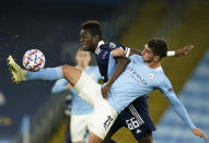 Manchester City's Ferran Torres, front, duels for the ball with Olympiacos' Pape Abou Cisse during the Champions League group C soccer match between Manchester City and Olympiacos at the Etihad stadium in Manchester, England, Tuesday, Nov. 3, 2020. (AP Photo/Dave Thompson)