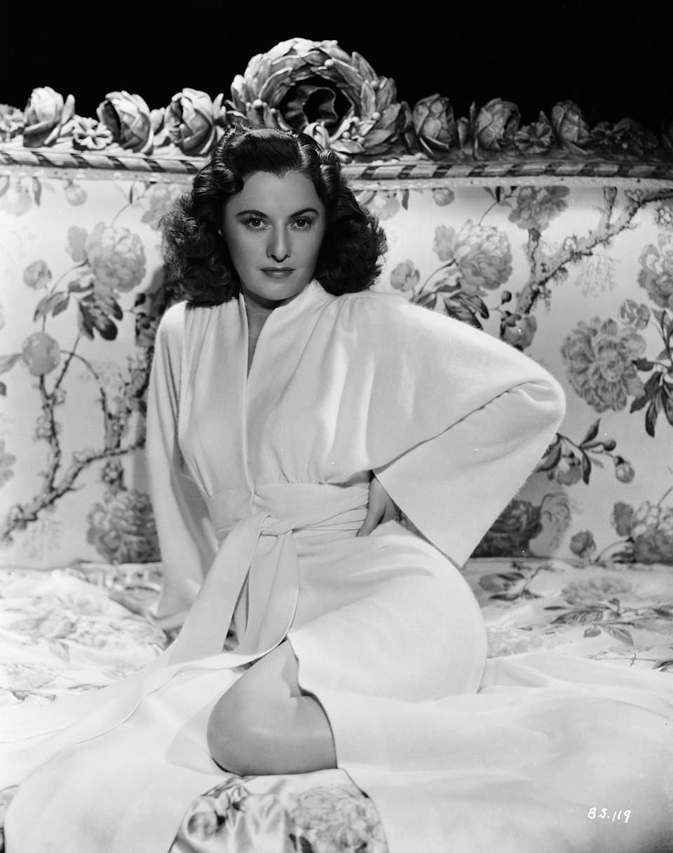 """Stanwyck wears a white belted robe in a publicity still for """"The Gay Sisters,"""" 1942."""