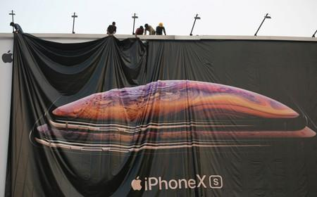 FILE PHOTO: Workers adjust a hoarding of the newly launched iPhone XS in Ahmedabad