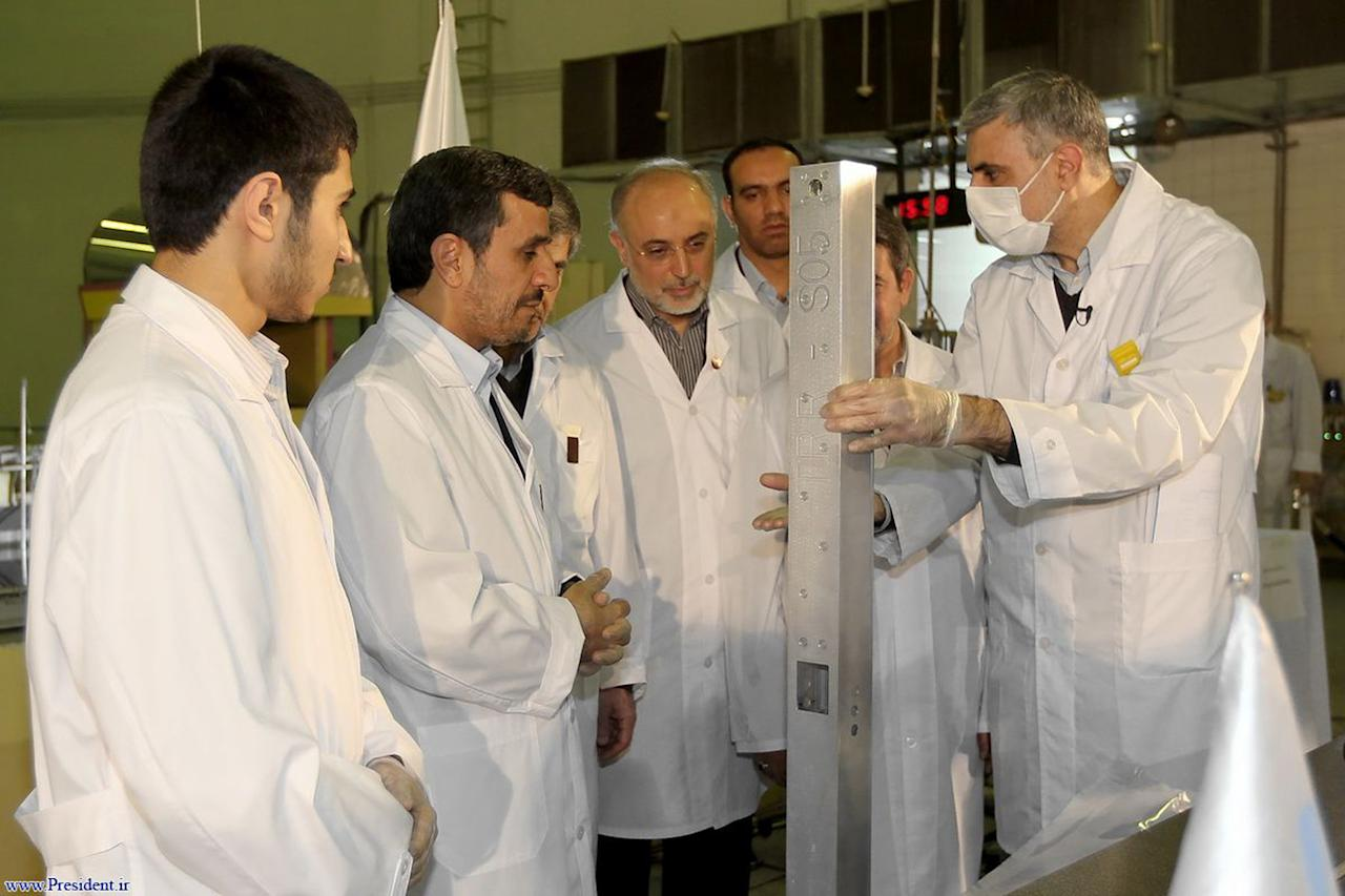 FILE - In this Wednesday Feb. 15, 2012 file photo, released by the Iranian President's Office, claims to show Iranian President Mahmoud Ahmadinejad, second left being escorted by technicians during a tour of Tehran's research reactor centre in northern Tehran, Iran. Iran's denials that it is trying to develop nuclear weapons carry a distinctly hollow ring among its foes as the U.N. nuclear watchdog piles on worries: Complaining about limits on inspection access and reporting that Tehran is expanding its nuclear fuel labs. But, as Israel increasingly weighs the option of a military strike, Western leaders wary of another Middle East conflict may have to pay closer attention to the claims. (AP Photo/Iranian President's Office, File)