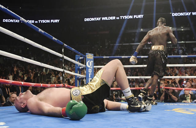 Tyson Fury lies on the canvas after being knocked down by Deontay Wilder during the 12th round of their WBC heavyweight championship boxing match in L.A. The bout ended in a draw. (AP Photo/Mark J. Terrill, File)