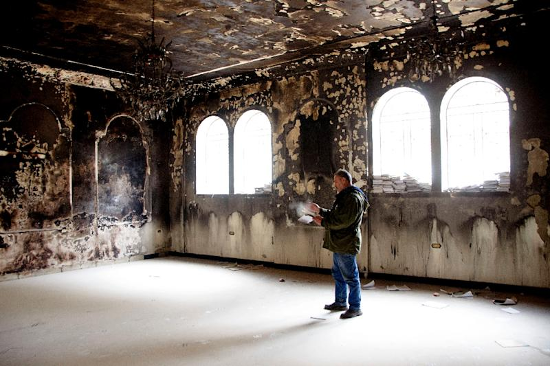 Nabil al-Aash inspects the war-scarred Saint George Church, a testament to the seven-year conflict that has left more than 360,000 people dead (AFP Photo/Maher AL MOUNES)