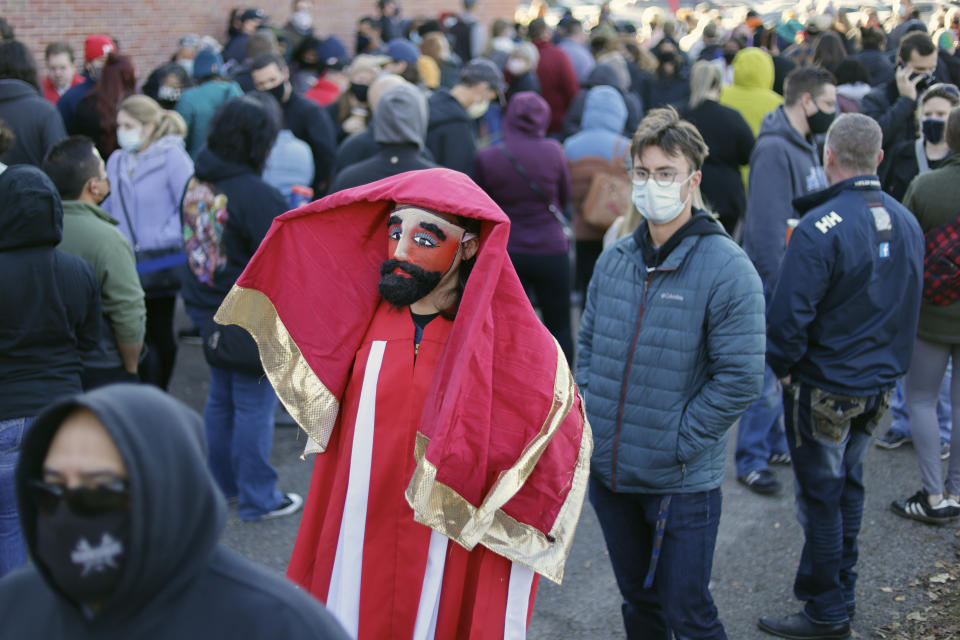 Adam Fogerty wears a costume on Halloween, as he stands in line with others to vote early, at the Douglas County Election Commission office in Omaha, Neb., Saturday, Oct. 31, 2020. (AP Photo/Nati Harnik)