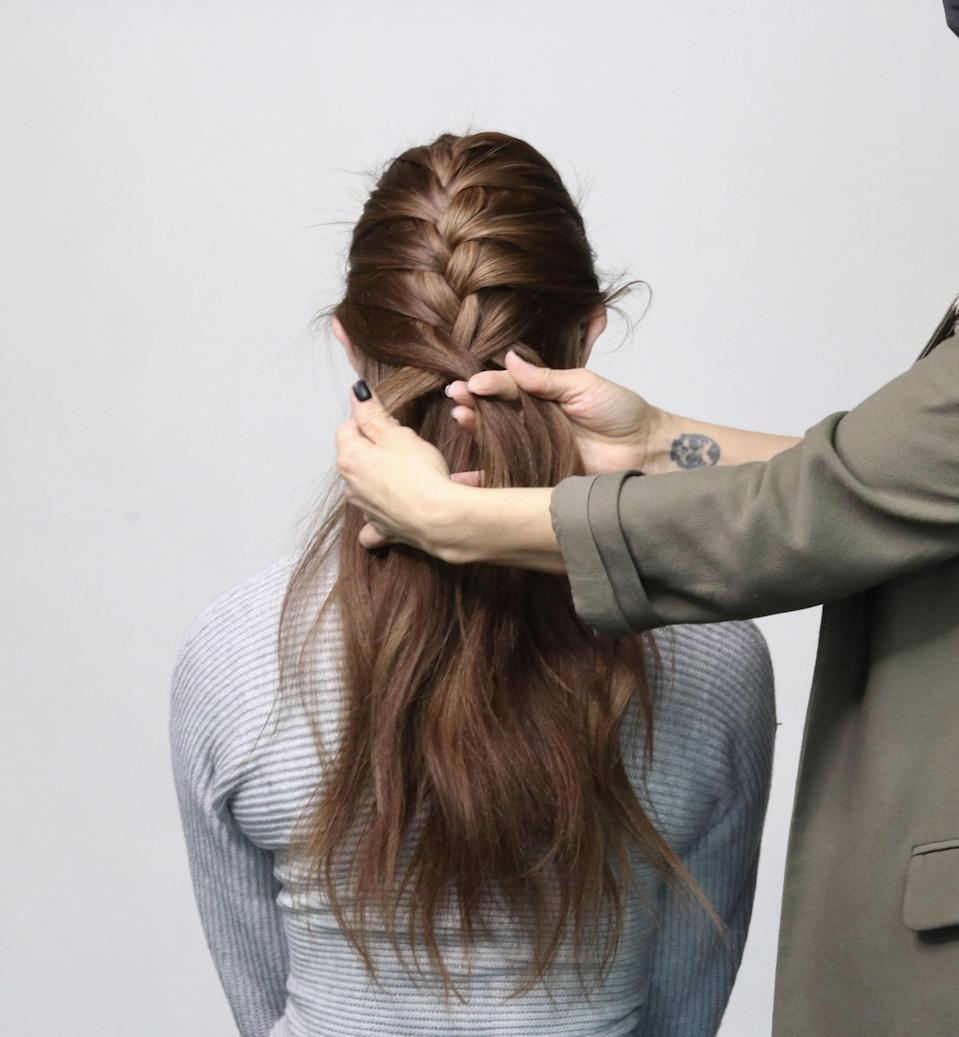 <p>Every time you cross over, grab a one-inch section of hair behind your ear and near the hairline on your neck, and work it into the weaved section. Continue to cross the larger piece of hair on either side over the middle section of the braid.</p>