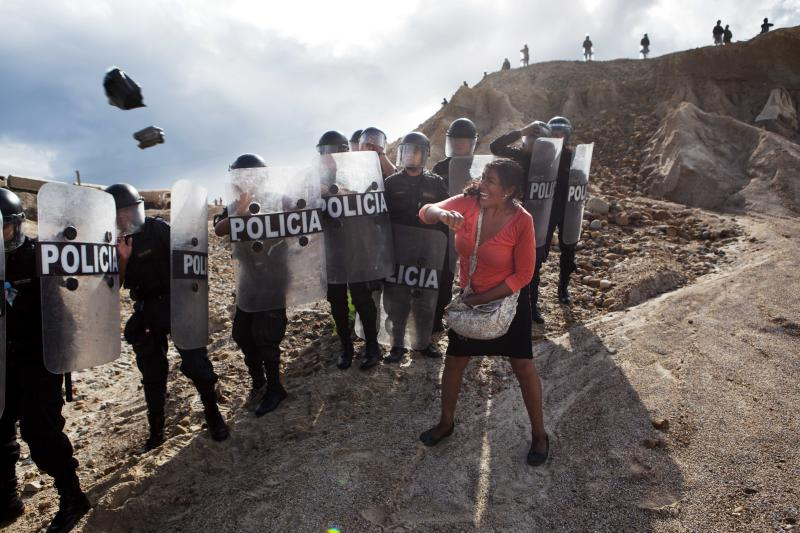 A woman throws a rock and a bag at riot policemen who block her way home in Huepetuhe district in Peru's Madre de Dios region in Peru, Monday, April 28, 2014. Soldiers, police and marines have begun destroying illegal gold mining machinery in Peru's southeastern jungle region of Madre de Dios. Authorities began enforcing a ban on illegal mining Monday in the Huepetuhe district. Before the deadline, miners clashed with police while intermittently blocking traffic on the Interoceanic Highway that links the Pacific with Brazil. (AP Photo/Rodrigo Abd)