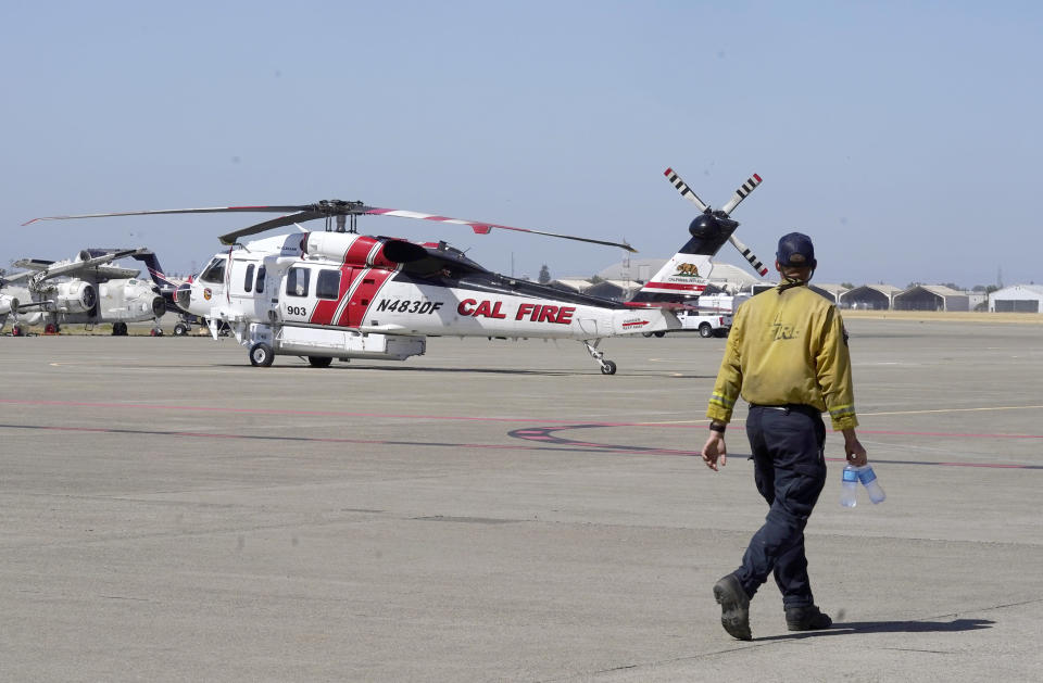 A Sikorsky Firehawk helicopter sits on the tarmac at the California Department of Forestry and Fire Protection's Sacramento Aviation Management Unit based at McClellan Airpark in Sacramento, Calif., Friday, July 23, 2021. Firefighters are trying to become smarter in how they prepare for the drought- and wind-driven wildfires that have become more dangerous across the American West in recent years, including by adding aircraft like the Sikorsky Firehawk helicopters or military surplus C-130 transport aircraft retrofitted to drop fire retardant. (AP Photo/Rich Pedroncelli))