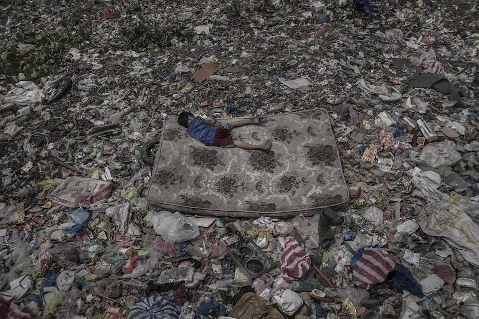 <p>A child who collects recyclable material lies on a mattress surrounded by garbage floating on the Pasig River, in Manila, Philippines. (Mário Cruz) </p>