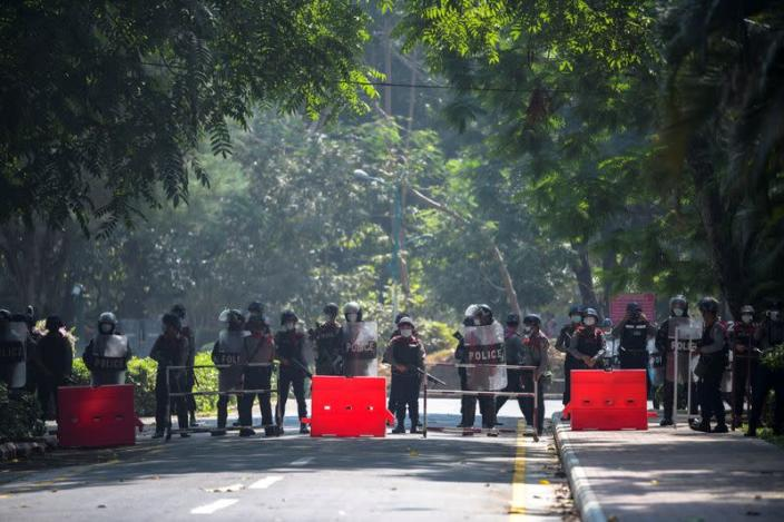 Riot police officers stand guard during a rally against the military coup at the University of Yangon