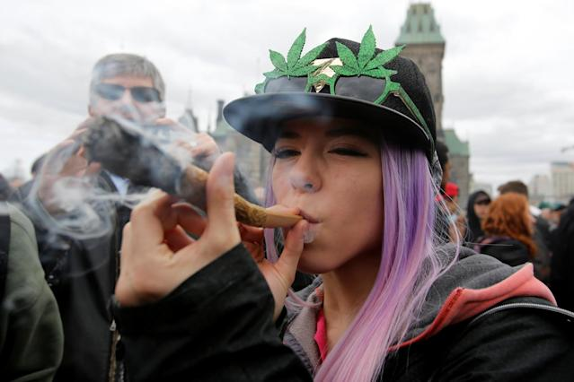 A woman smokes marijuana during the annual 4/20 marijuana rally on Parliament Hill in Ottawa, Ontario, Canada, April 20, 2017. (Reuters)