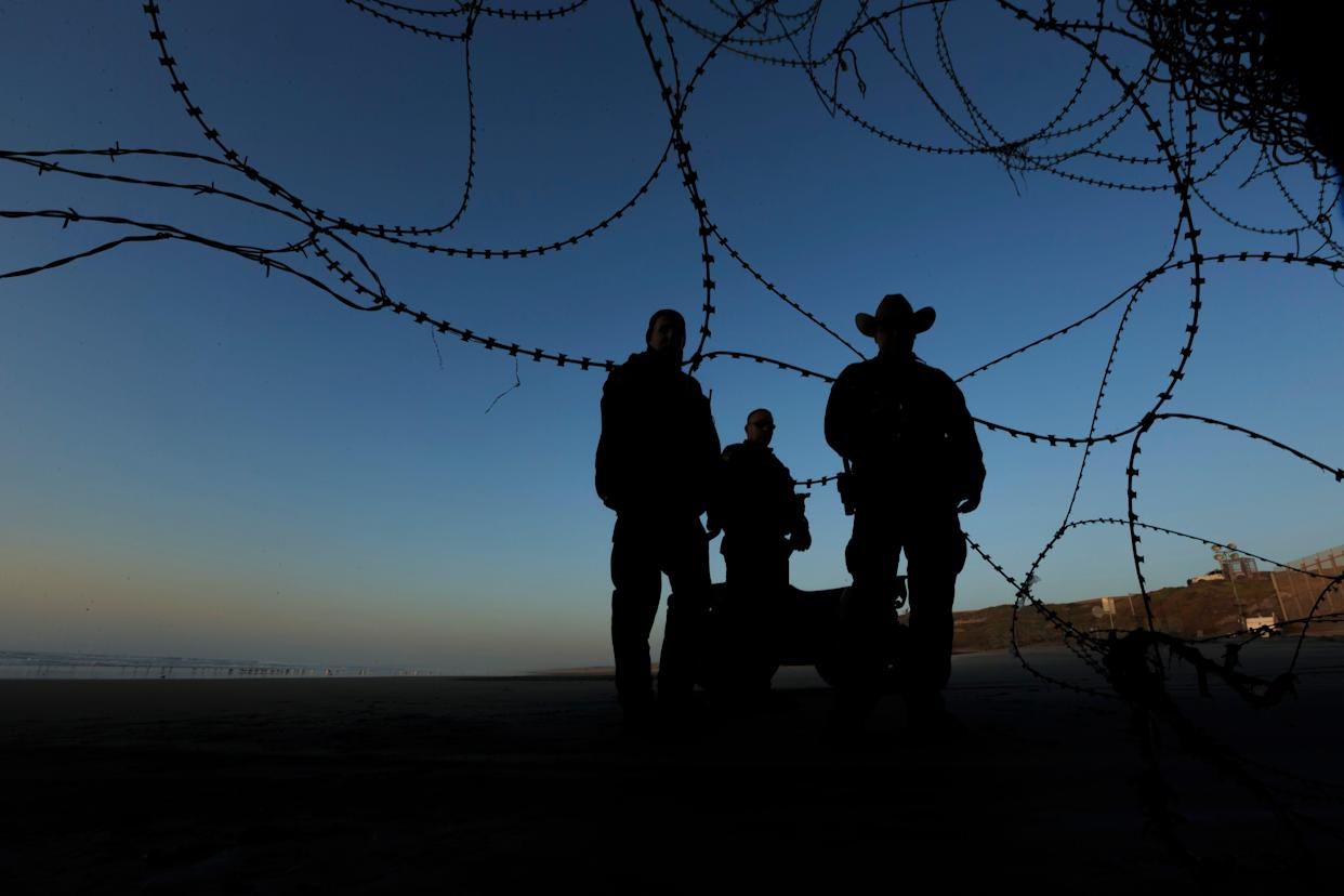 Border patrol officers stand at the beach on the U.S. side of the fence between San Diego and Tijuana, Mexico, Monday, Dec. 24, 2018.