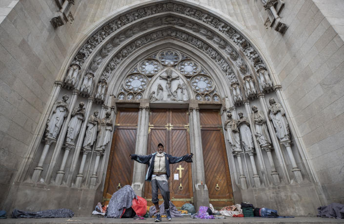 A homeless man gestures to the camera after waking up from sleeping overnight outside the Cathedral, amid the spread of the new coronavirus in Sao Paulo, Brazil, Thursday, May 7, 2020. According to the Sao Paulo municipal office of social assistance and welfare, at least 22 homeless people have died of COVID-19 in the past few weeks. (AP Photo/Andre Penner)