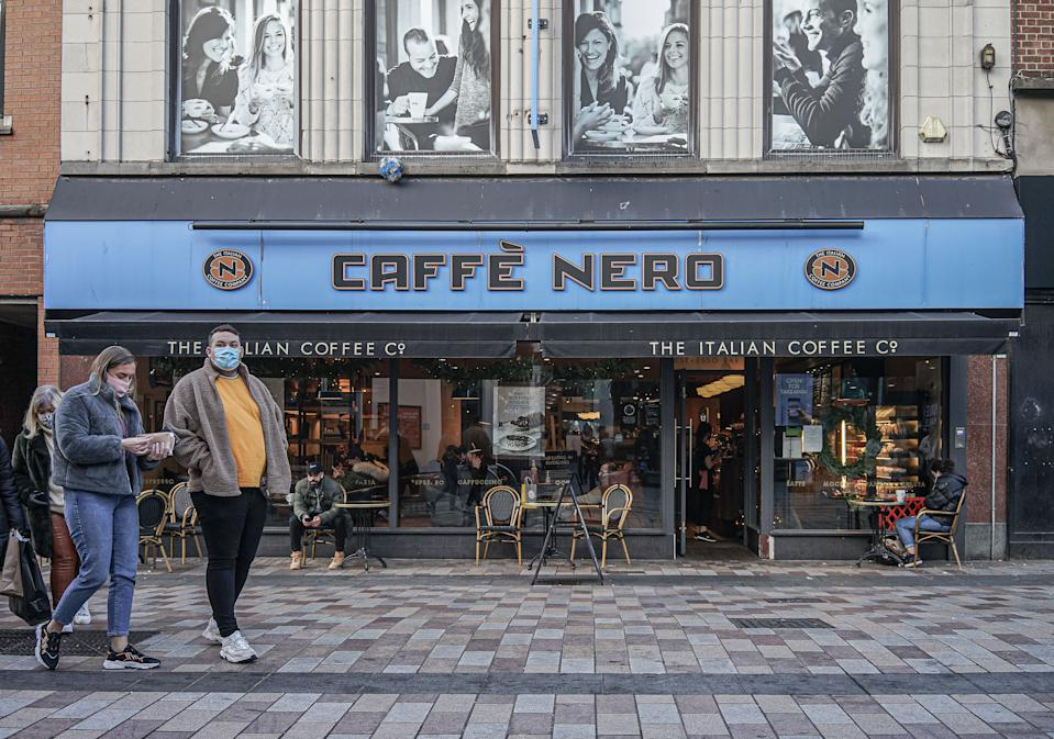 BELFAST, ANTRIM, UNITED KINGDOM - 2020/12/22: A couple wearing face masks as a precaution against the spread of covid-19 walking past the Caffe Nero Coffee Shop. (Photo by Michael McNerney/SOPA Images/LightRocket via Getty Images)