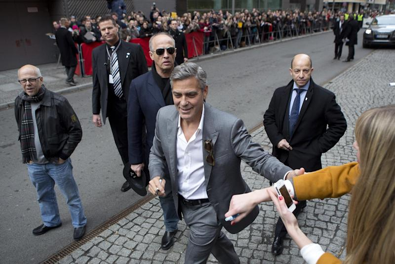 Actor George Clooney reaches out to a fan as he arrives for the photo call of the film The Monuments Men during the International Film Festival Berlinale, in Berlin, Saturday, Feb. 8, 2014. (AP Photo/Axel Schmidt)