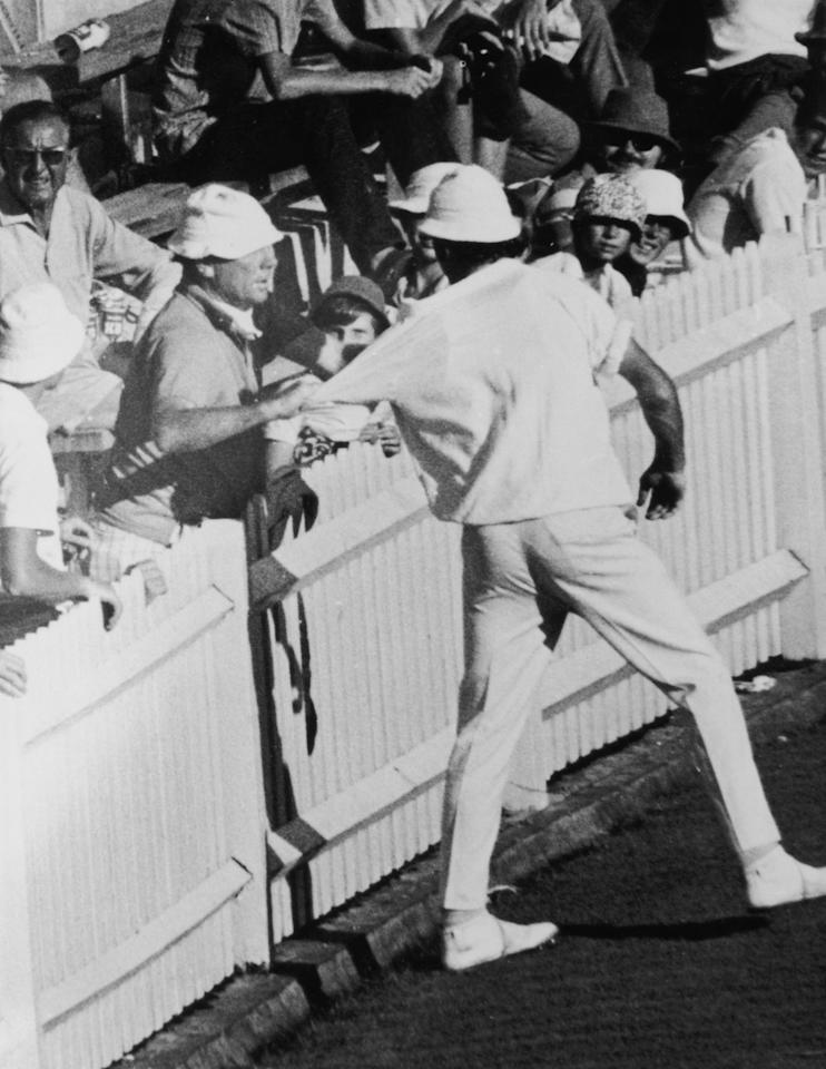 England bowler John Snow is grabbed by a member of the crowd after Australian batsman Terry Jenner had been hit on the head by one of his 'bumper' balls during the Final Test match in Sydney, 20th February 1971. Illingworth led his team off the pitch in protest. (Photo by Central Press/Hulton Archive/Getty Images)