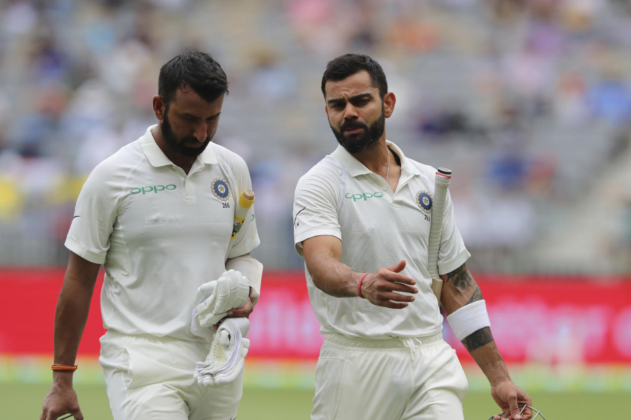 India's Cheteshwar Pujara, left, and Virat Kohli talk as they leave the ground for the tea break in the second cricket test between Australia and India in Perth, Australia, Saturday, Dec. 15, 2018. (AP Photo/Trevor Collens)