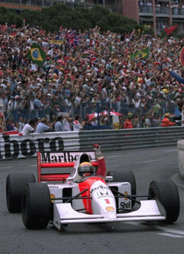 FILE - In this May 31, 1992 file photo, Brazilian driver Ayrton Senna raises his fist to salute the crowd after he won the Monaco Formula One Grand Prix on his McLaren-Honda. Brazil's adoration of Ayrton Senna transcends sports. Senna won three Formula One titles in 1988, 1990 and '91 all with McLaren. He moved to the Williams team for his tragic 1994 season. Despite his career being cut short when he was 34, his 41 wins stand third all-time behind Michael Schumacher's 91 and rival Alain Prost's 51. He died at the 1994 San Marino Grand Prix. (AP Photo/JEAN-MARC FOLLETE, File)