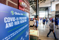 A COVID-19 prevention protocol sign hangs in the concourse of Globe Life Field before the Texas Rangers home opener baseball game against the Toronto Blue Jays Monday, April 5, 2021, in Arlington, Texas. The Texas Rangers are set to have the closest thing to a full stadium in pro sports since the coronavirus shut down more than a year ago. (AP Photo/Jeffrey McWhorter)