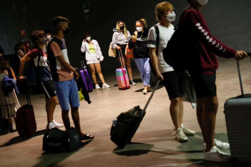 Young people wait to take a voluntary antigen test for the coronavirus disease (COVID-19) after coming back from vacationing in Salou at the bus station in Pamplona