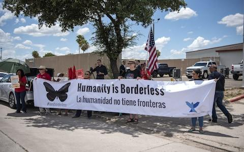 """<span>Demonstrators hold a large banner that reads """"Humanity Is Borderless,"""" outside of a U.S. Border Patrol station in McAllen,</span> <span>Credit: Bloomberg </span>"""