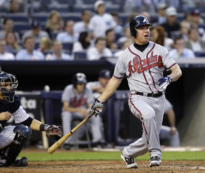 Atlanta Braves' Chipper Jones follows through on a fourth-inning RBI double against the New York Yankees in a baseball game at Yankee Stadium in New York, Tuesday, June 19, 2012. At left is Yankees catcher Russell Martin. (AP Photo/Kathy Willens)