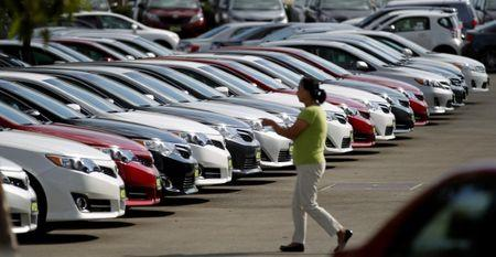 A woman walks by vehicles for sale at a Toyota dealership in Pasadena