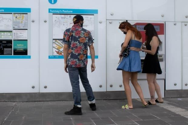 People purchase tickets outside the Tunney's Pasture LRT station in Ottawa. (Trevor Pritchard/CBC - image credit)