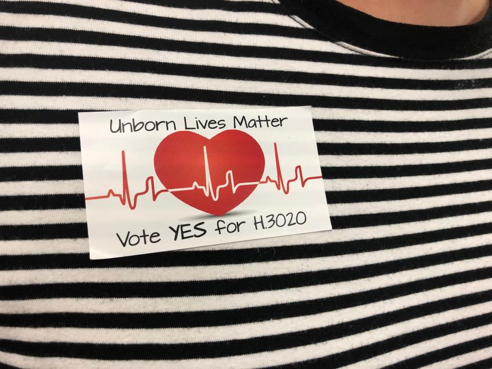 Supporters of a bill banning abortions in South Carolina after a fetal heartbeat is detected wore similar stickers at a state Senate subcommittee public hearing on Tuesday, Sept. 10, 2019, in Columbia, S.C. The bill has already passed the House and is supported by the governor. (AP Photo / Jeffrey Collins)