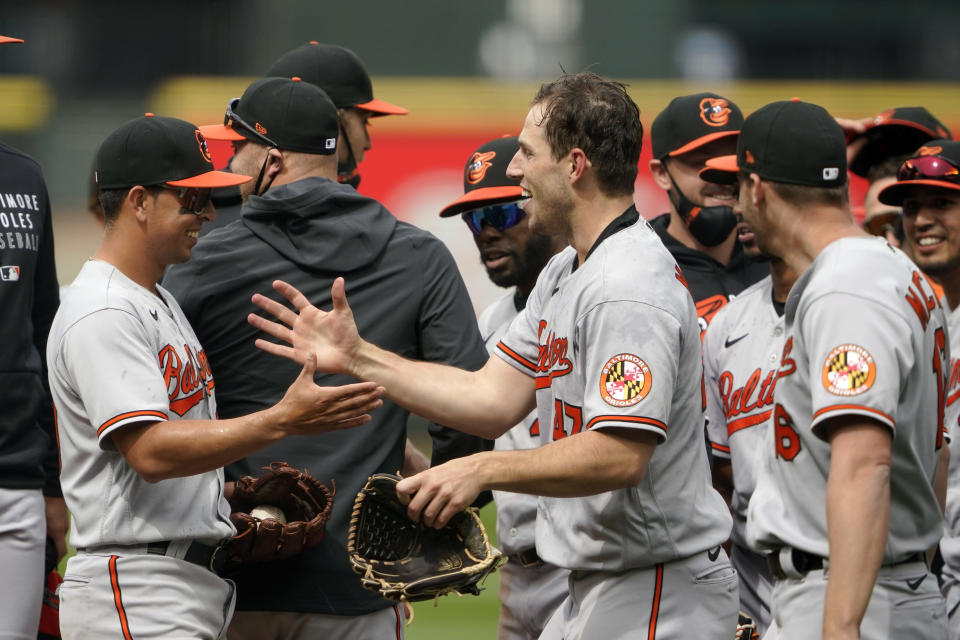 Baltimore Orioles starting pitcher John Means, center, greets shortstop Ramon Urias, left, after Means threw a no-hitter baseball game against the Seattle Mariners, Wednesday, May 5, 2021, in Seattle. Urias made the final out, snagging a line drive hit by by Seattle Mariners' J.P. Crawford. The Orioles won 6-0. (AP Photo/Ted S. Warren)