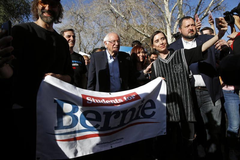 Democratic presidential candidate Sen. Bernie Sanders, I-Vt., leads supporters to an early voting location after a campaign event at the University of Nevada, Las Vegas, Tuesday, Feb. 18, 2020, in Las Vegas. (AP Photo/Patrick Semansky)
