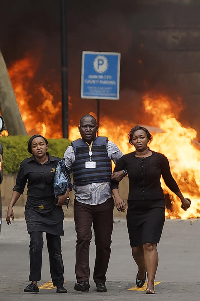 Security forces help civilians flee the scene as cars burn behind, at a hotel complex in Nairobi, Kenya Tuesday, Jan. 15, 2019. Terrorists attacked an upscale hotel complex in Kenya's capital Tuesday, sending people fleeing in panic as explosions and heavy gunfire reverberated through the neighborhood. (AP Photo/Ben Curtis)