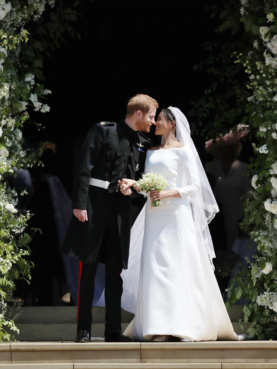 WINDSOR, UNITED KINGDOM - MAY 19:  Prince Harry and Meghan Markle kiss on the steps of St George's Chapel in Windsor Castle after their wedding in St George's Chapel at Windsor Castle on May 19, 2018 in Windsor, England. (Photo by Jane Barlow - WPA Pool/Getty Images)