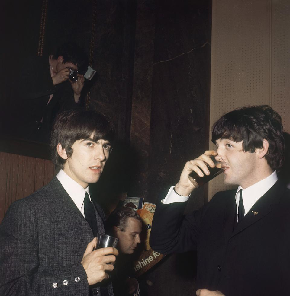 George Harrison, left, and Paul McCartney of the Beatles have refreshments at Australia House, London, England, Wednesday, April 22, 1964. (AP Photo)